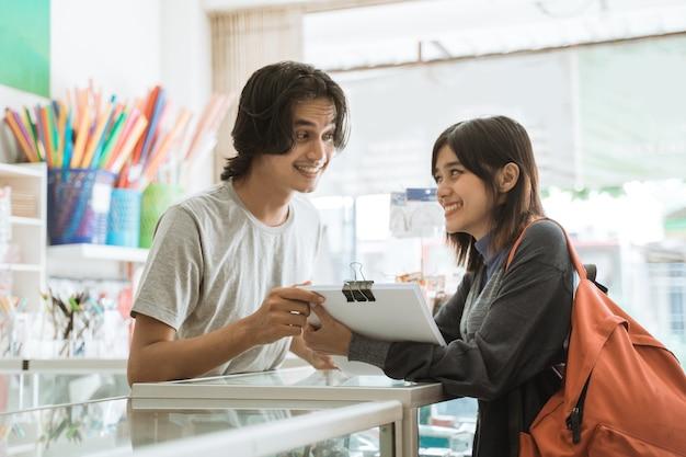 Молодая девушка, посещающая магазин канцелярских товаров, разговаривает с кассиром-мужчиной