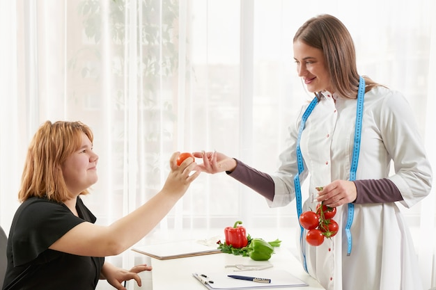 Young girl visiting nutritionist to lose weight with the help of diet program.