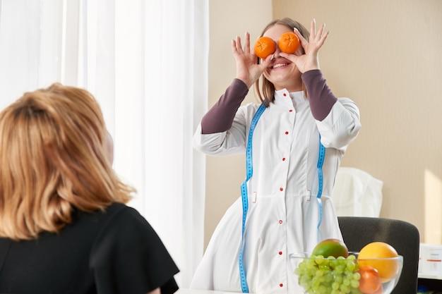ダイエットプログラムの助けを借りて体重を減らすために栄養士を訪問している若い女の子