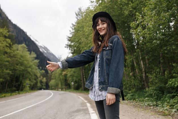 히치 하이킹 산의 배경에 차를 기다리는 어린 소녀