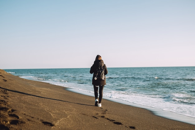 若い女の子は海の近くのビーチを歩く