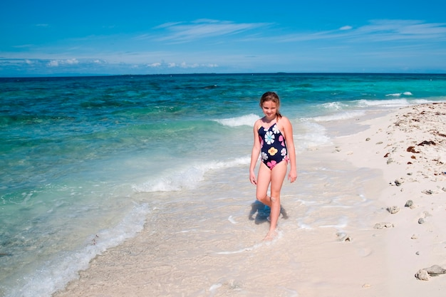 Young girl walking along beach at belizean isle in belize