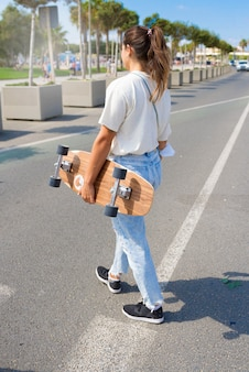 Young girl walking down the street with a skateboard