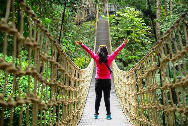 Молодая девушка гуляет по мосту в тропическом лесу подвесной бридж переход через реку в лесу
