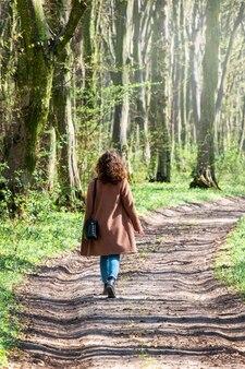 Молодая девушка гуляет по лесной дороге