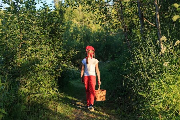 자작 나무 껍질 바구니를 들고 녹색 숲을 통해 길을 걷는 어린 소녀