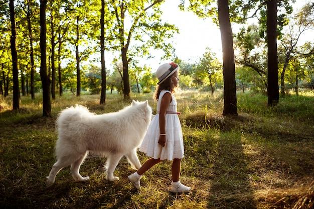 Молодая девушка гуляет, играя с собакой в парке на закате.