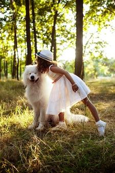 若い女の子が歩いて、夕暮れ時の公園で犬と遊んで。