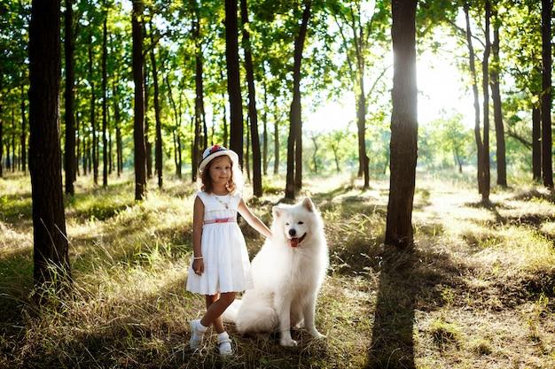 Ragazza che cammina, giocando con il cane nel parco al tramonto.