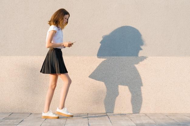 大きなステップで歩くと携帯電話でテキストを読む少女