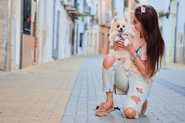 Young girl walking with her white fluffy pomeranian.