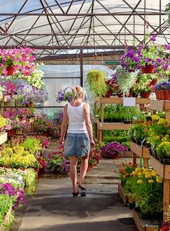 Молодая девушка идет босиком по садовому центру