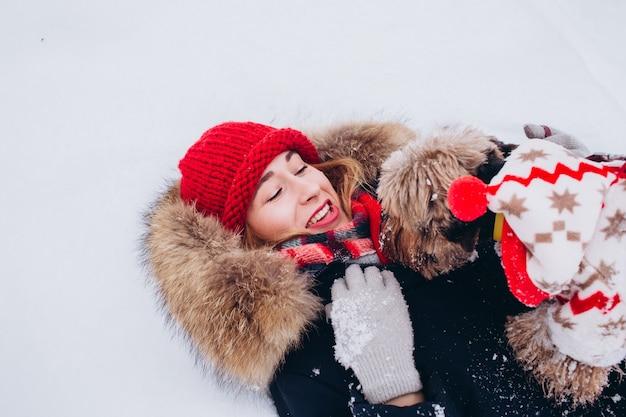 若い女の子は、クリスマスセーターを着て犬と一緒に冬に低い森の中を歩きます