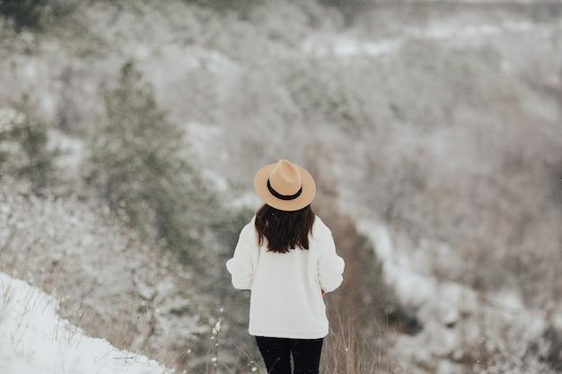 若い女の子は冬の雪の森を歩きます。背面図。