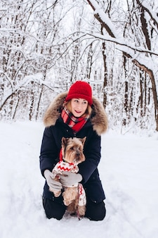 Young girl walks in the lower woods in winter with dog wearing a christmas sweater