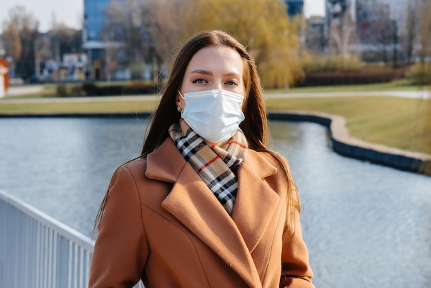 A young girl walks in a mask during the pandemic and coronovirus. quarantine.