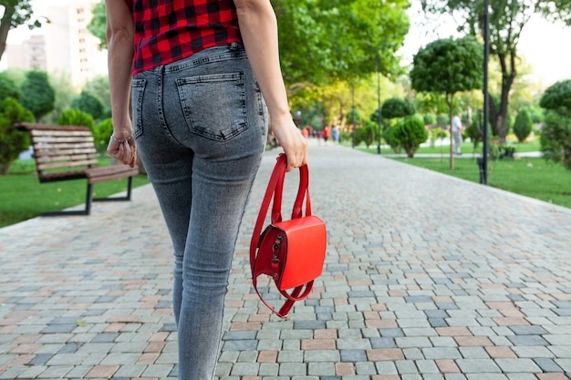 Young girl walks in the park with a handbag
