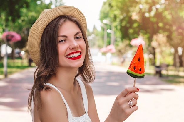 A young girl walks in the park with a lollipop in the form of watermelon