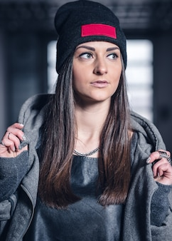 Young girl in a warm hat with long dark hair and a gray sweatshirt with a hood in a hangar