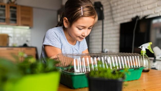 Молодая девушка наблюдает за выращиванием сельскохозяйственных культур дома