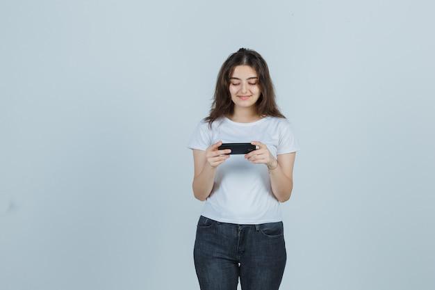 Ragazza che guarda video sul cellulare in t-shirt, jeans e che sembra felice, vista frontale.