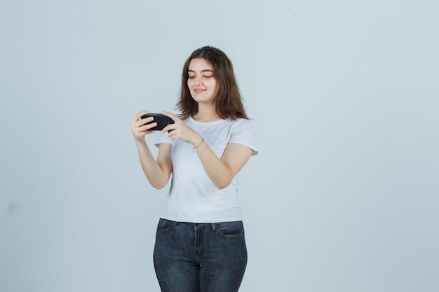Молодая девушка смотрит видео на мобильном телефоне в футболке, джинсах и выглядит счастливым, вид спереди.