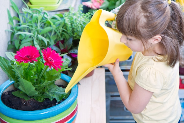 笑顔の鉢植えの花植物に水をまく少女