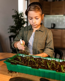 Young girl watering sprouts at home