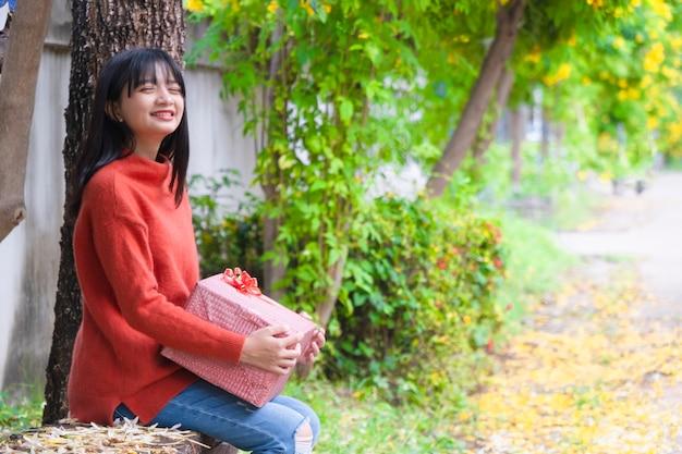 若い女の子は、ギフトボックスと木の下に座っているオレンジ色のセーターを着ています。