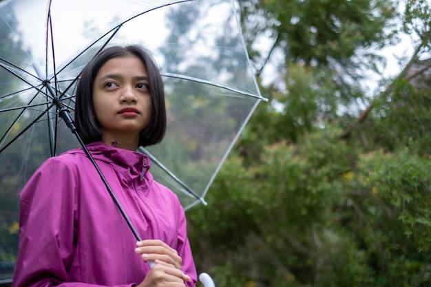若い女の子は雨の中でピンクのコートレインを着ています。