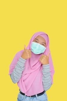 若い女の子は黄色の背景にピンクのヒジャーブを着用します