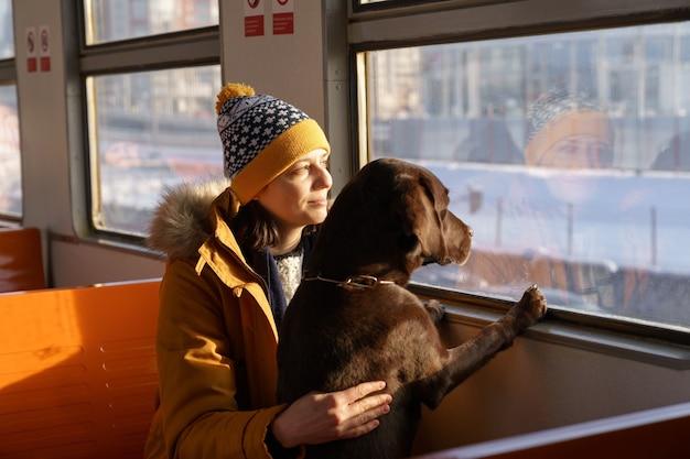 Молодая девушка в зимней одежде сидит в пригородном поезде со своей милой собакой и смотрит в окно