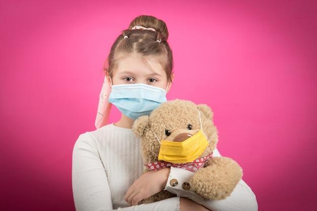 Молодая девушка в медицинской маске с коронавирусом держит плюшевого мишку, изолированного на розовом