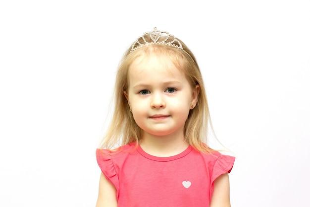 귀여운 미소로 왕관과 핑크색 드레스를 입고 어린 소녀