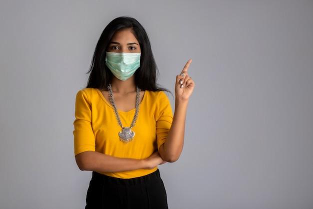포즈, 포인팅 및 회색 배경에 뭔가 보여주는 의료 얼굴 마스크를 쓰고 어린 소녀.