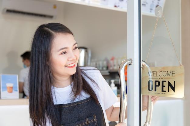 Молодая девушка в фартуке. счастливая девушка открывает двери в кафе и смотрит на деревянную доску открытого знака