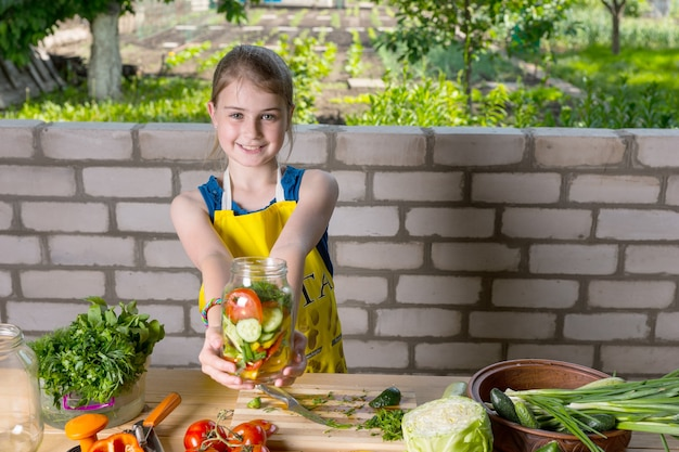 エプロンを身に着けている少女は、漬物と保存の準備のために新鮮なみじん切りの野菜で満たされた瓶を笑顔で保持します