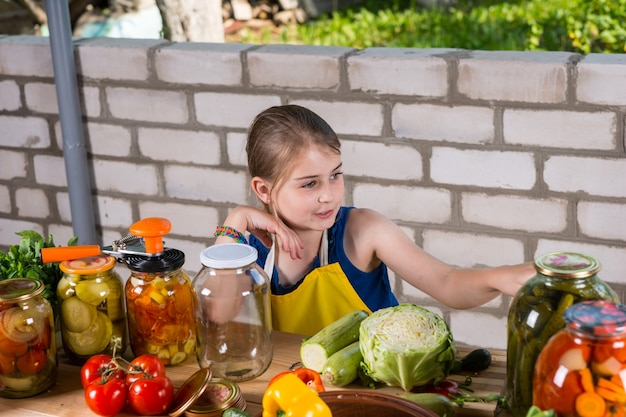 庭のレンガの壁の近くに立ってエプロンを着て、ガラスの瓶で保存または酸洗いのために新鮮な野菜を準備している若い女の子