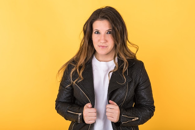 Young girl wearing black leather jacket on yellow.