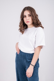 Young girl wearing blank tshirt white wall background fashion mockup high quality photo