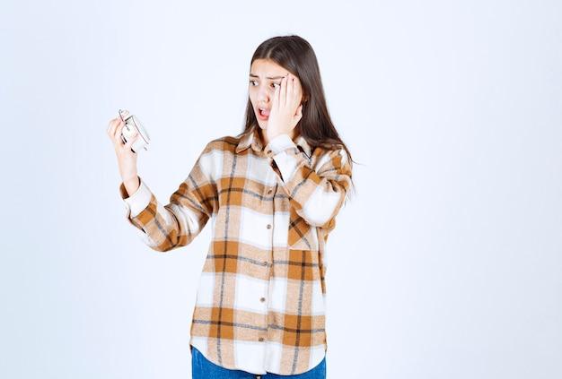 カジュアルな服を着て時間を見て頬を抱えている少女。