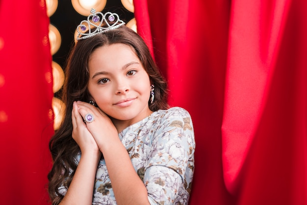 Young girl wearing crown posing in front of red curtain