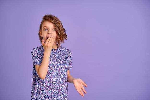 Молодая девушка в платье с цветочным принтом на фиолетовом шокированном рте с конусом рукой