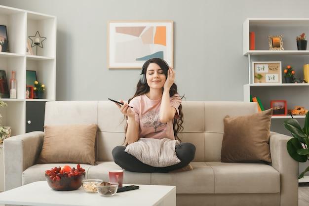 Молодая девушка в наушниках держит телефон, сидя на диване за журнальным столиком в гостиной