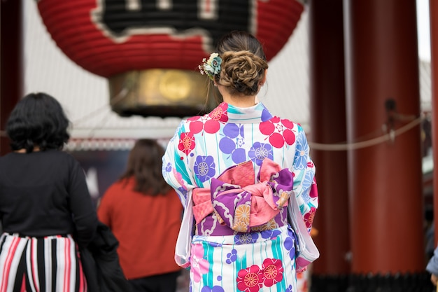 Young girl wearing japanese kimono standing in front of sensoji temple in tokyo