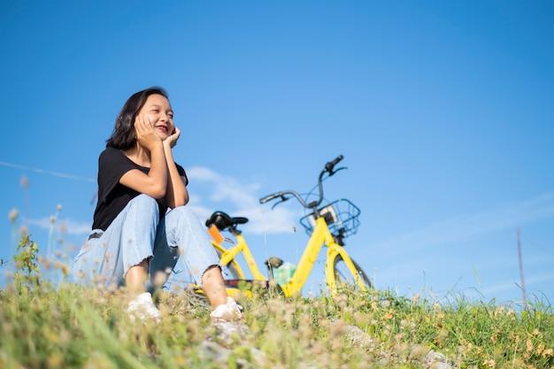 Молодая девушка в джинсовой черной футболке сидит с велосипедом в парке с голубым небом