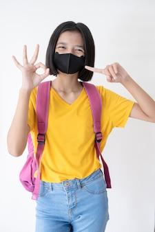 白い背景にバックパックでマスクを着た若い女の子。
