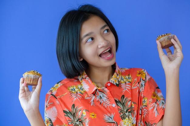 オレンジ色のシャツを着て、ケーキを手に保持している若い女の子