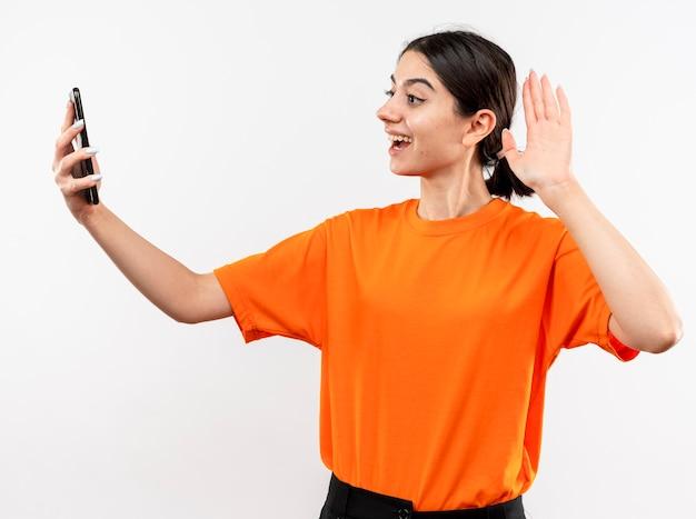白い壁の上に立っている手で手を振って幸せでポジティブな笑顔のビデオ通話を持っているオレンジ色のtシャツを着ている若い女の子