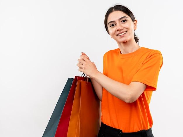 Ragazza che indossa la maglietta arancione che tiene i sacchetti di carta sorridenti felici e positivi che stanno sopra il muro bianco